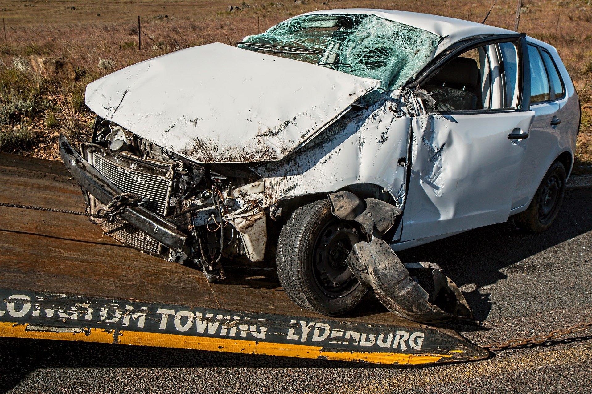 Foto de um carro branco com a parte frontal totalmente danificada, em cima da parte traseira de um guincho. Imagem ilustrativa para texto perda total.