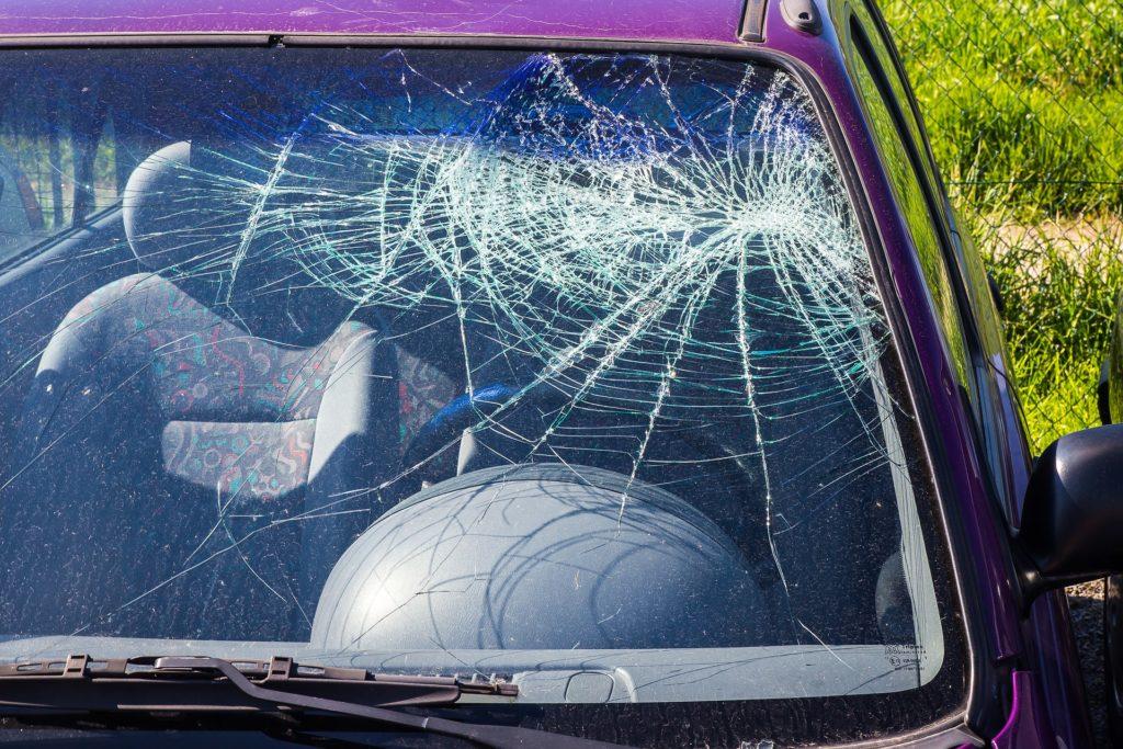 Foto do vidro quebrado de um carro vermelho escuro. Vemos apenas a parte superior esquerda do carro e uma grama ao fundo. Imagem ilustrativa para texto seguro para carro de leilão.