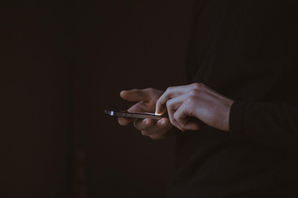 Foto de uma pessoa toda de preto, com um fundo preto segurando um celular na mão. Imagem ilustrativa para texto seguro de portáteis.