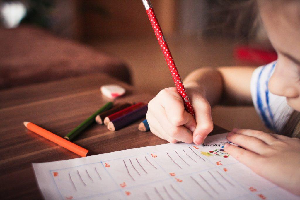 Foto de uma menina com lapis na mão escrevendo um papel. Vemos uma mesa de madeira, com lápis coloridos ao lado. A menina está de blusa branca e azul, com um fundo desfocado.