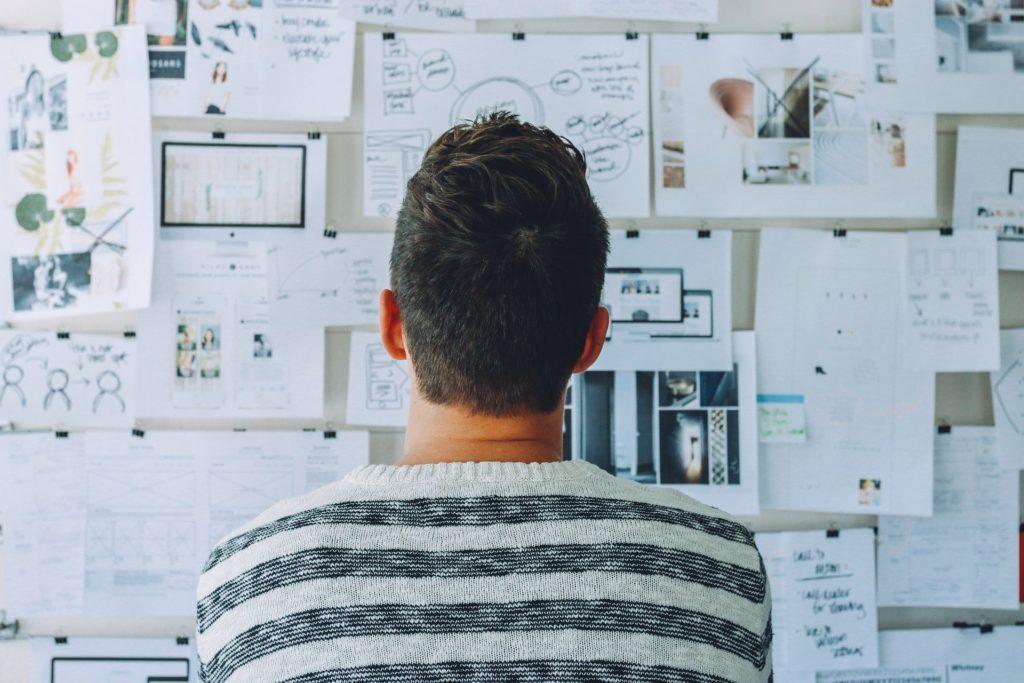 Homem de blusa listada preta e branca, olhando para um quadro com vários papeis pregados. Imagem ilustrativa para texto seguro de vida individual.