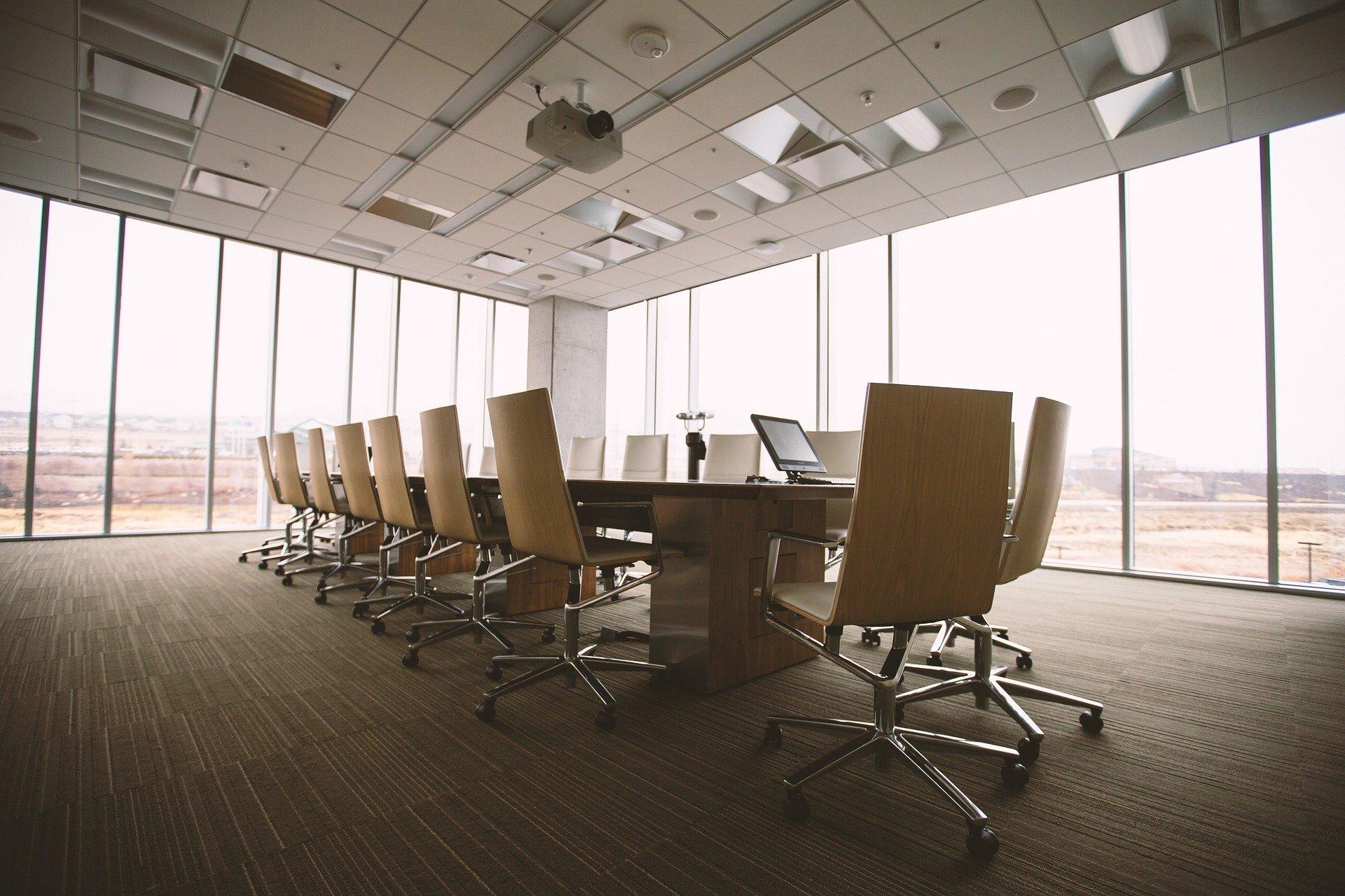 Sala ampla de reuniões em uma empresa, vemos paredes de vidro ao redor, no centro temos uma mesa grande com várias cadeiras beges. Imagem ilustrativa para texto seguro empresarial.
