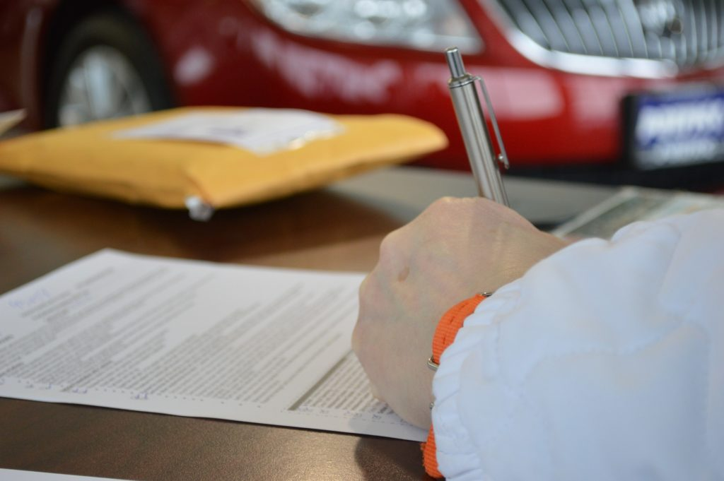 Foto de uma mão, com roupa branca, segurando uma caneta prata enquanto assina um contrato em uma mesa preta. Ao lado, vemos um pacote amarelo e ao fundo um carro vermelho. Imagem ilustrativa para texto corretora e seguradora.