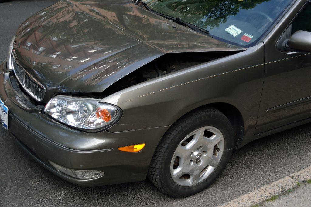 Imagem de um carro cinza em uma rua. Há danos no capô que está amassado. Imagem ilustrativa para o artigo tipos de seguros.