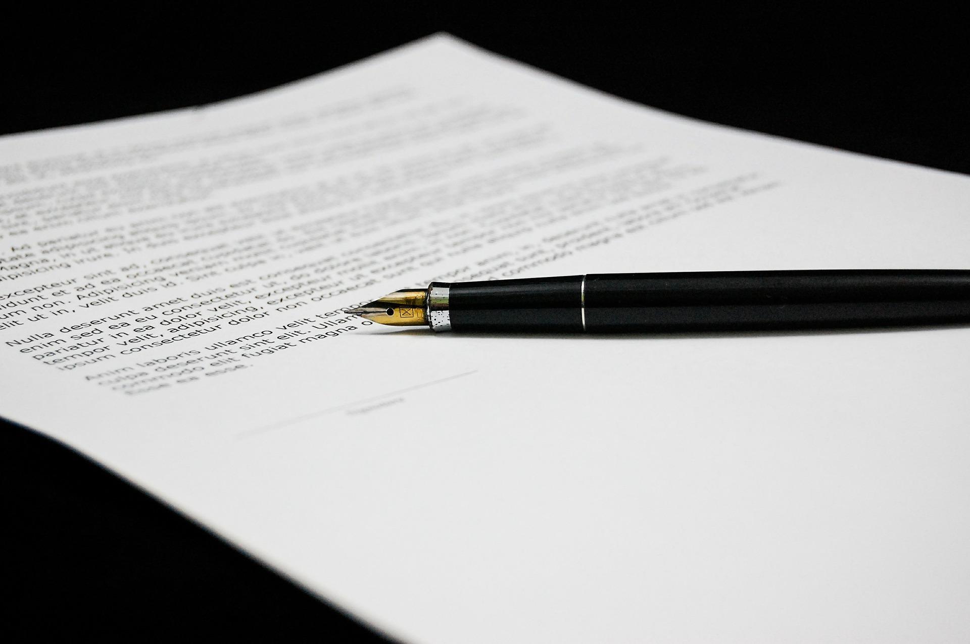 Foto de uma folha de documento em cima de uma mesa preta, com uma caneta também preta em cima. Imagem ilustrativa para texto endosso de seguro.