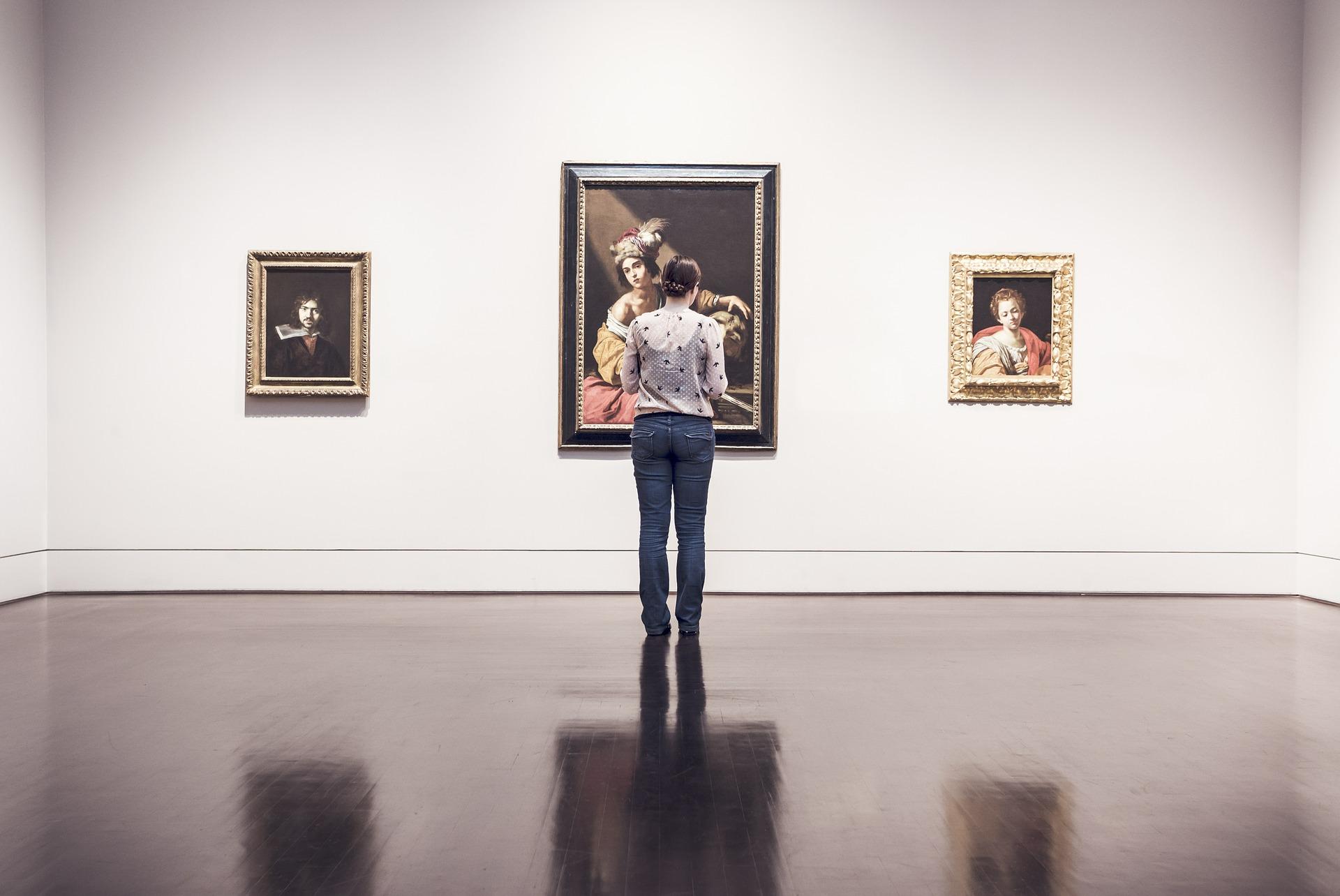 Foto de uma moça com blusa cinza e calça jeans no meio de uma galeria com quadros de artes na parede branca e chão de madeira. Imagem ilustrativa para texto seguro obras de arte.