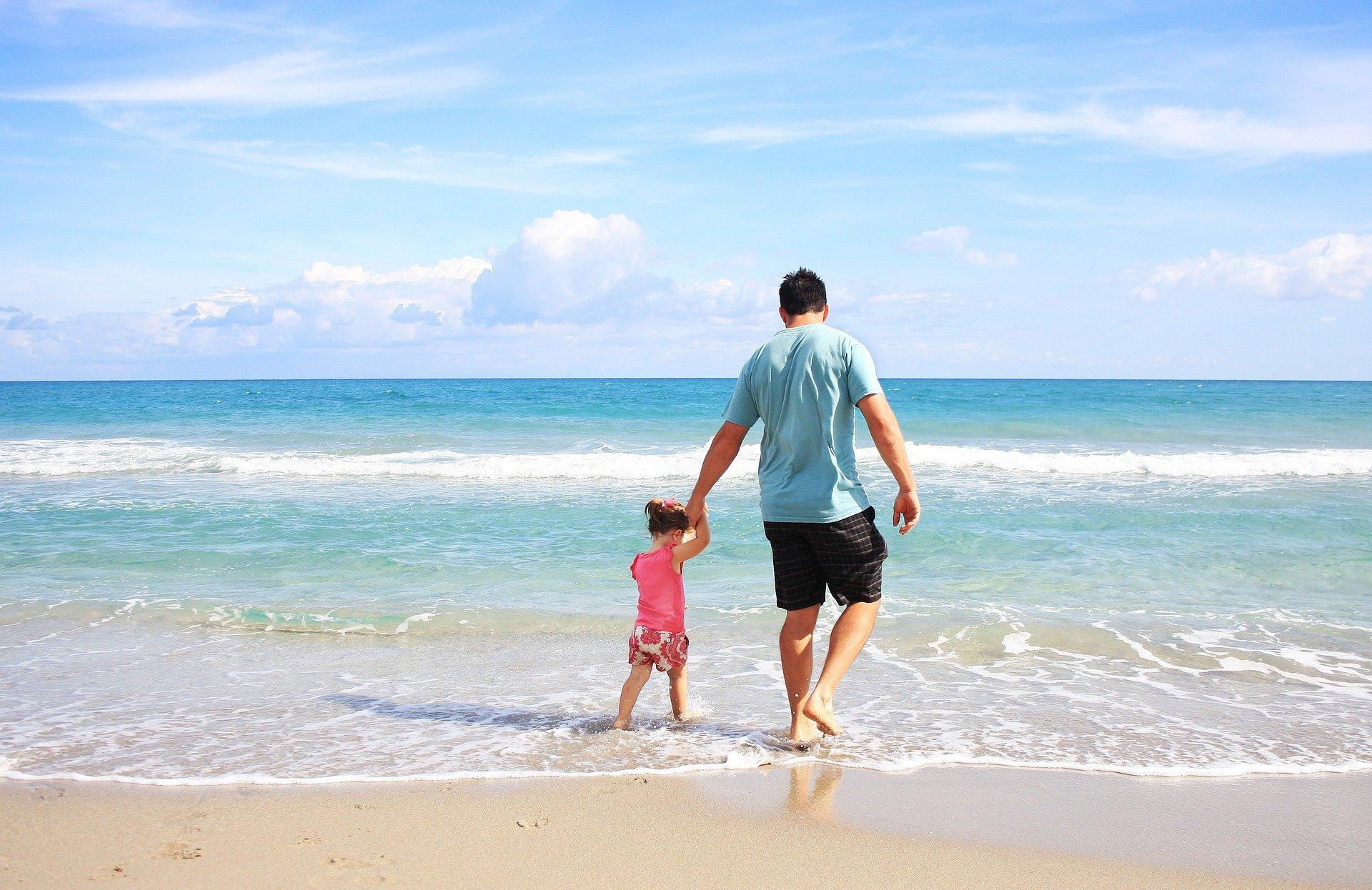 Foto de um homem de blusa azul e bermuda preta, caminhando na beira do mar de mãos dadas com uma menina de roupa rosa. Imagem ilustrativa para texto tipos de seguro de vida.