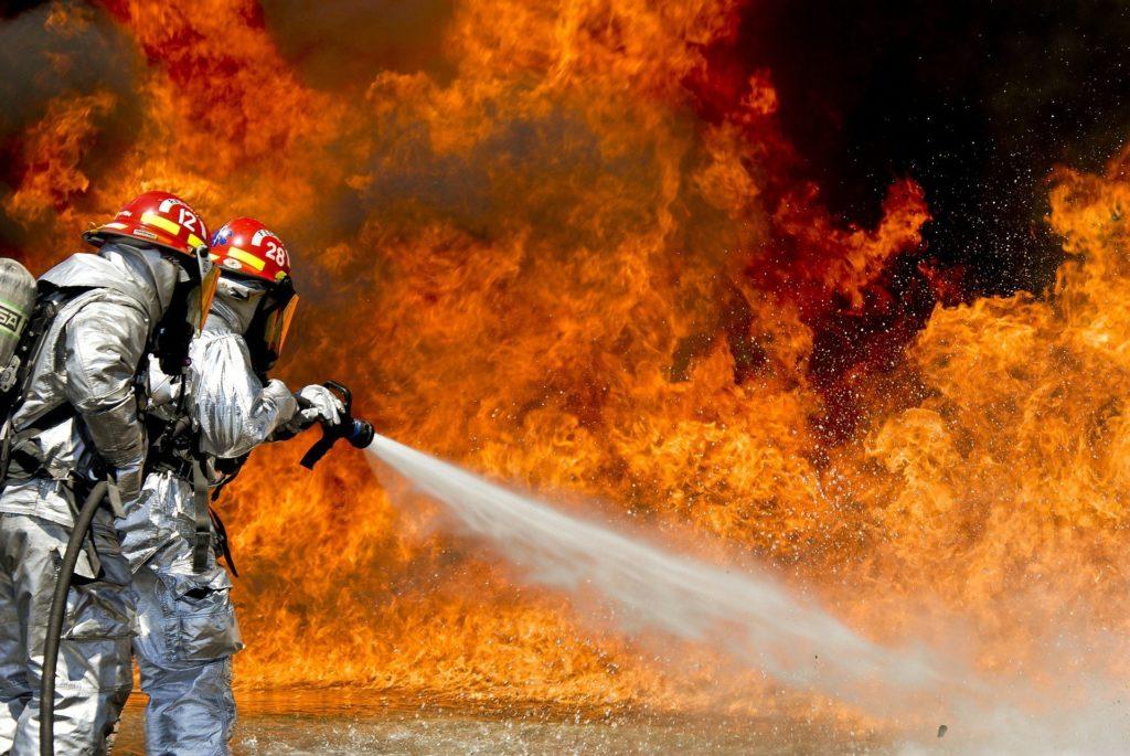 Dois bombeiros de roupa branca, segurando uma mangueira enquanto tentam apagar um incêndio. Ilustração do texto seguro empresarial.