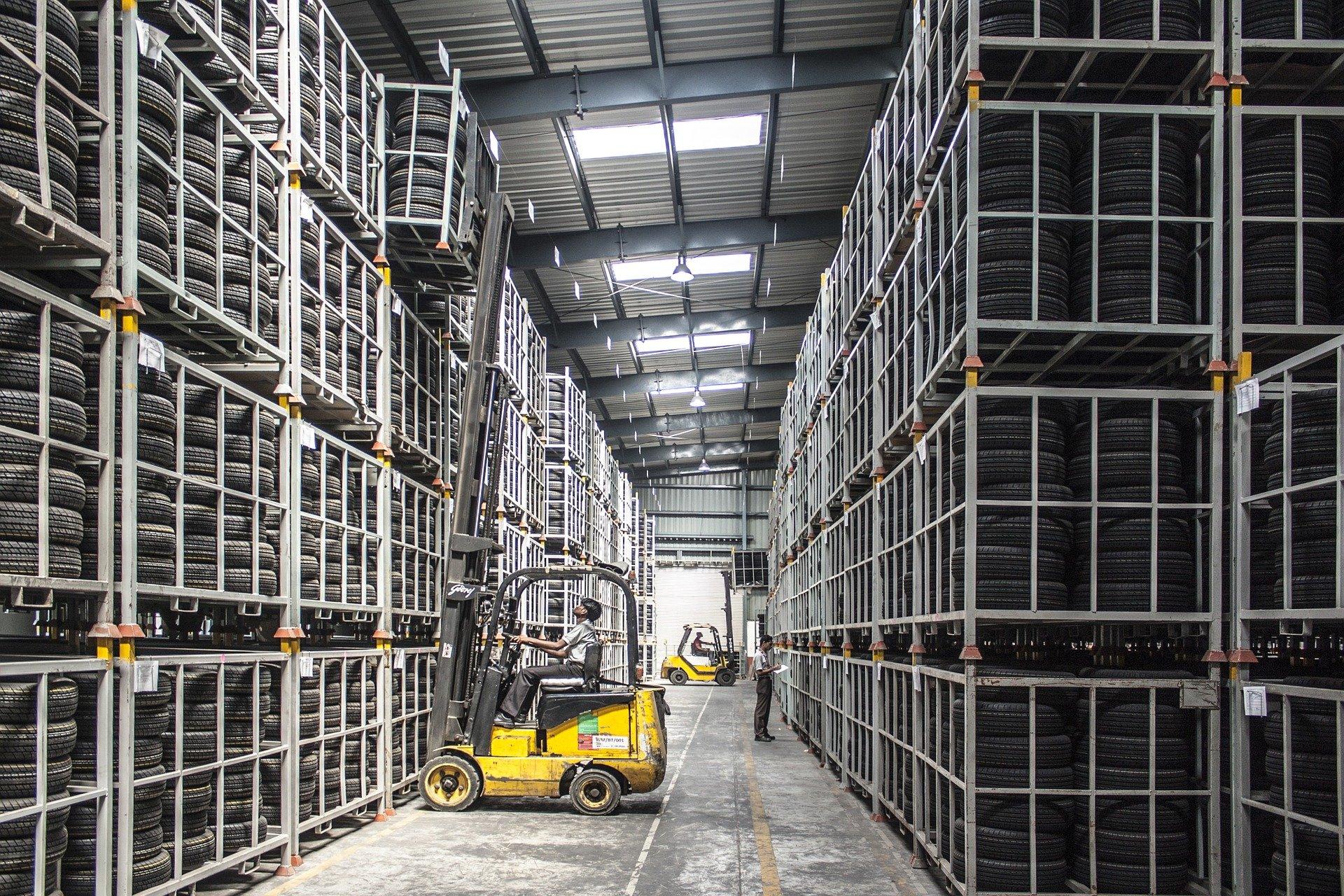 Foto de uma máquina amarela nos corredores de uma fábrica, com vários pneus empilhados dos lados. Imagem ilustrativa para texto seguro equipamentos.