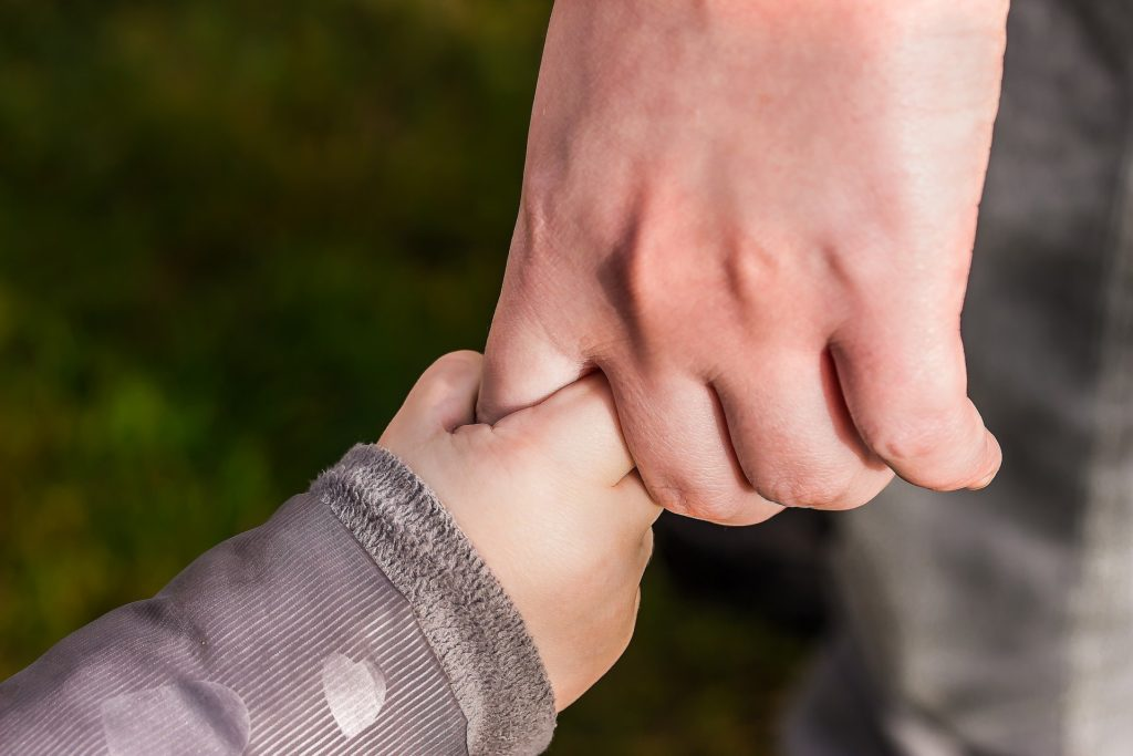 Foto da mão de uma criança com blusa cinza, segurando o dedo da mão de um adulto, ao fundo temos uma grama desfocada. Ilustração para o texto tipos de seguro.