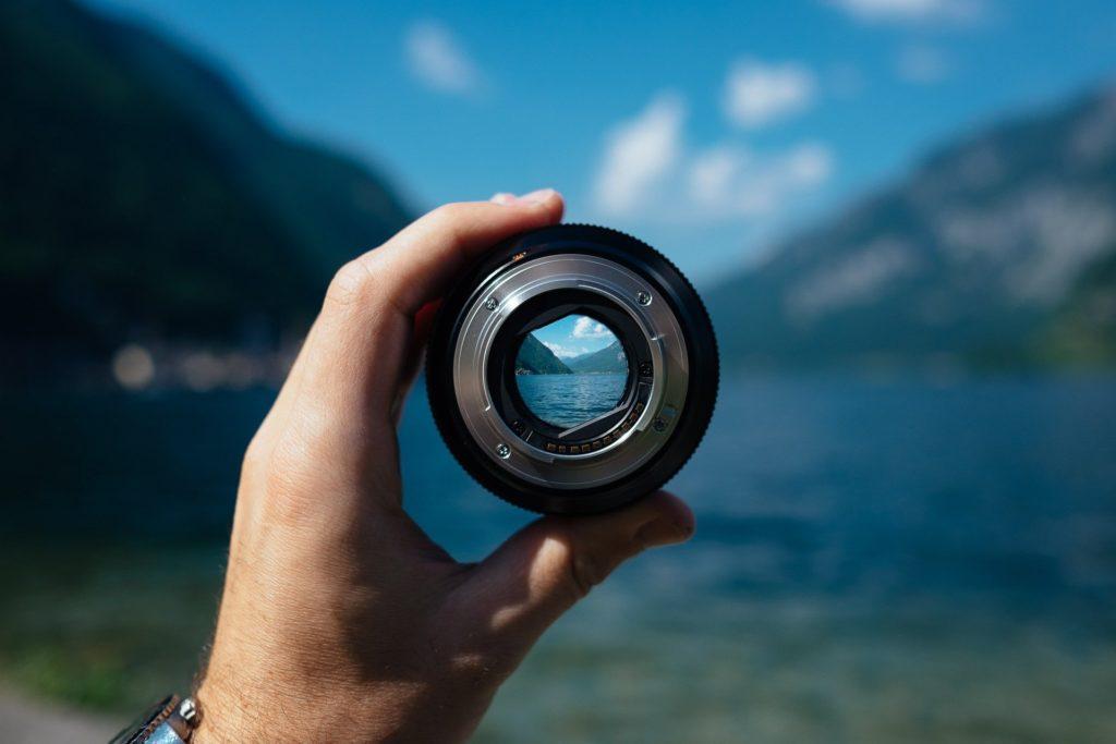 Foto de uma mão segurando uma lente de câmera com uma paisagem de lago ao fundo. Ilustração para o texto seguro de portáteis.