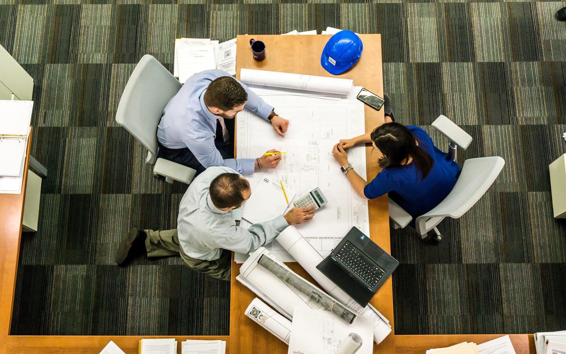 Foto de três pessoas, dois homens e uma mulher, reunidos em uma mesa de madeira com vários papeis, computar e capacete. Vemos um chão preto e cinza e outras mesas de madeira perto. Imagem ilustrativa para texto seguro roubo.