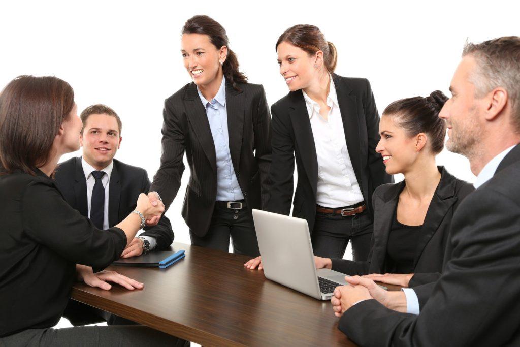 Várias pessoas de terno social preto reunidas ao redor de uma mesa de madeira conversando. Na mesa vemos também um computador e temos um fundo branco. Imagem ilustrativa para texto seguro empresarial.