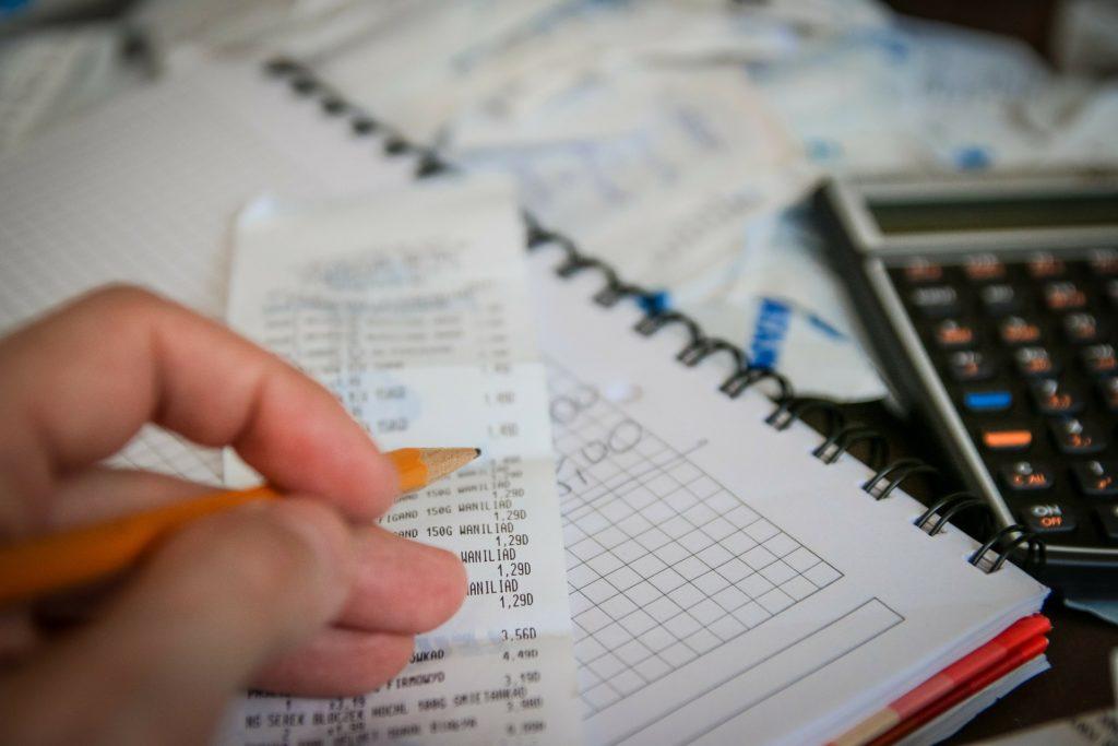 Foto de uma mão segurando um lápis, enquanto atrás temos uma nota fiscal, um caderno com contas, calculadora e mais notas.