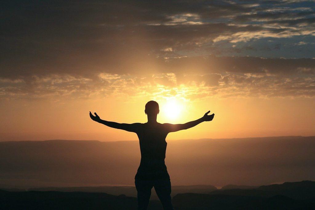 Foto de uma pessoa em cima de uma montanha em frente ao por do sol. Toda a imagem está em tons pretos e laranjas.