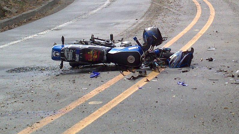 Foto de uma moto azul quebrada no meio de uma estrada. Imagem ilustrativa para texto tipos de seguros.