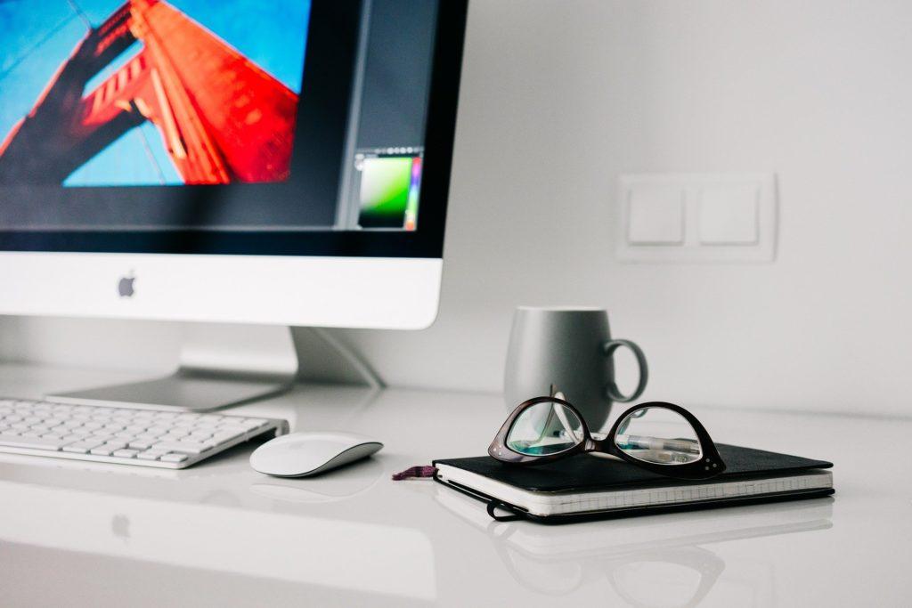 Foto de um computador branco, em uma mesa branca e com uma parede branca com fundo. Na mesa também vemos um caderno preto, um óculos e uma caneca cinza.