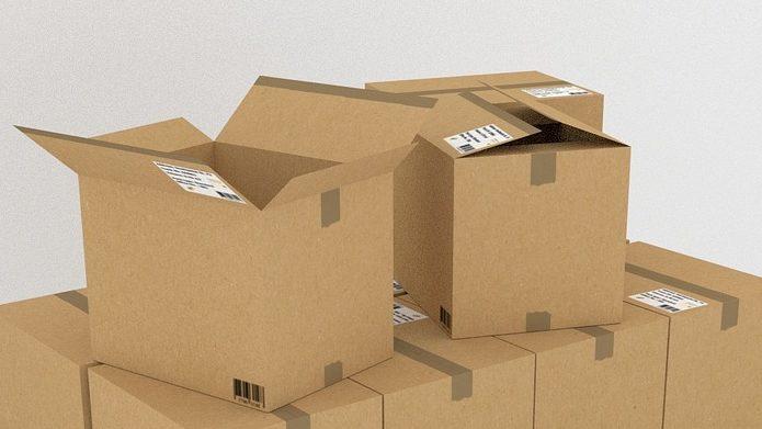 Foto de caixas de papelão empilhadas com um fundo branco, imagem ilustrativa para texto seguro empresarial.