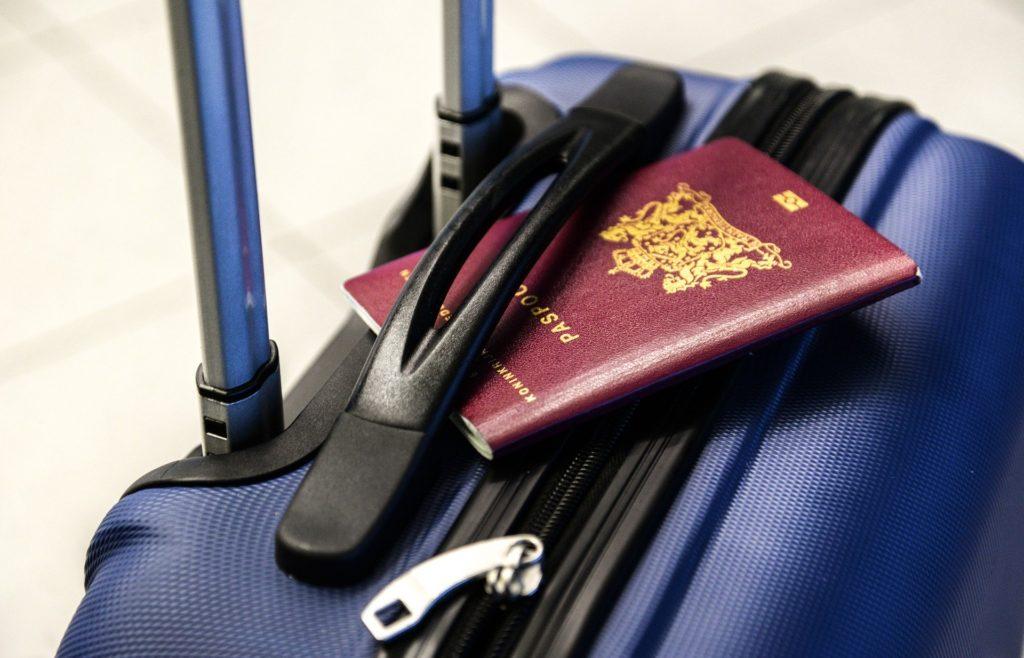 Foto de uma mala azul, com um passaporte vermelho escuro. Ao fundo vemos um chão bege.