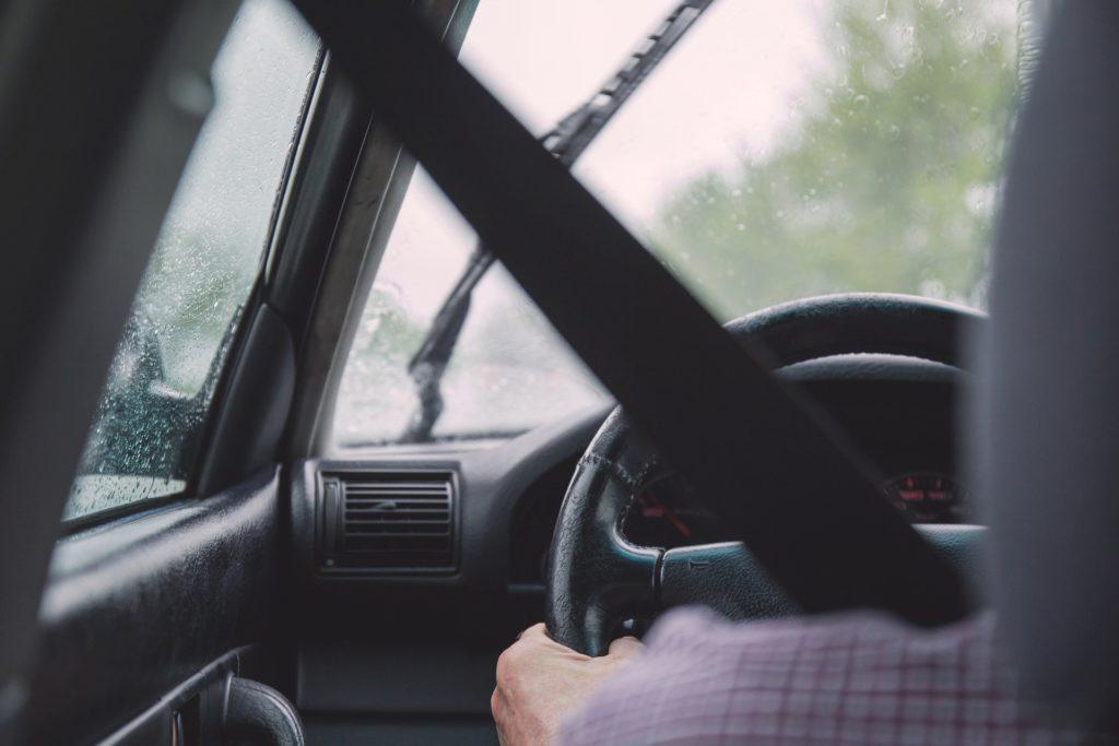 Foto de um motorista com camisa xadrez vermelha, segurando um volante enquanto dirige. Todos os detalhes do carro são pretos, no vidro vemos gotas de chuvas e uma paisagem ao fundo. Imagem ilustrativa para texto seguro de frota.