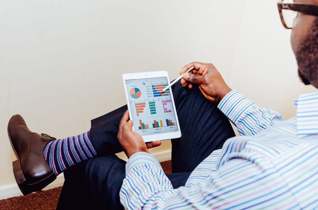 Foto de um homem de blusa azul e calça preta, sentado enquanto utiliza um tablet branco. O homem usa óculos e ao fundo tem uma parede branca. Imagem ilustrativa para texto mercado de seguros.