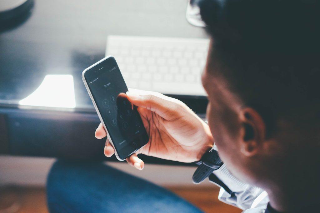 Foto de um homem segurando um celular. Vemos ao lado uma mesa preta e um teclado branco. Imagem ilustrativa para texto tipos de seguro de vida.