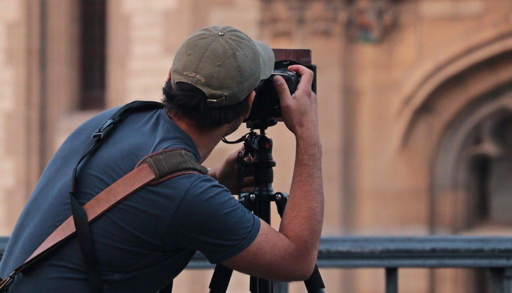 Foto de um home com blusa azul e boné bege trabalhando com uma câmera em frente a um monumento. Imagem ilustrativa para texto seguro de portáteis.