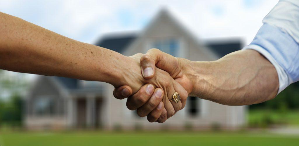 Foto de duas mãos se apertando, na mão da direita vemos um braço com blusa azul. No fundo temos uma casa desfocada, jardim e um céu azul. Imagem ilustrativa para texto corretora e seguradora.
