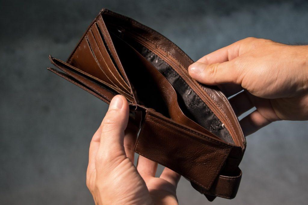 Foto de uma carteira sendo aberta, sem nenhum dinheiro dentro. Temos um fundo preto. Imagem ilustrativa para texto seguro prestamista.