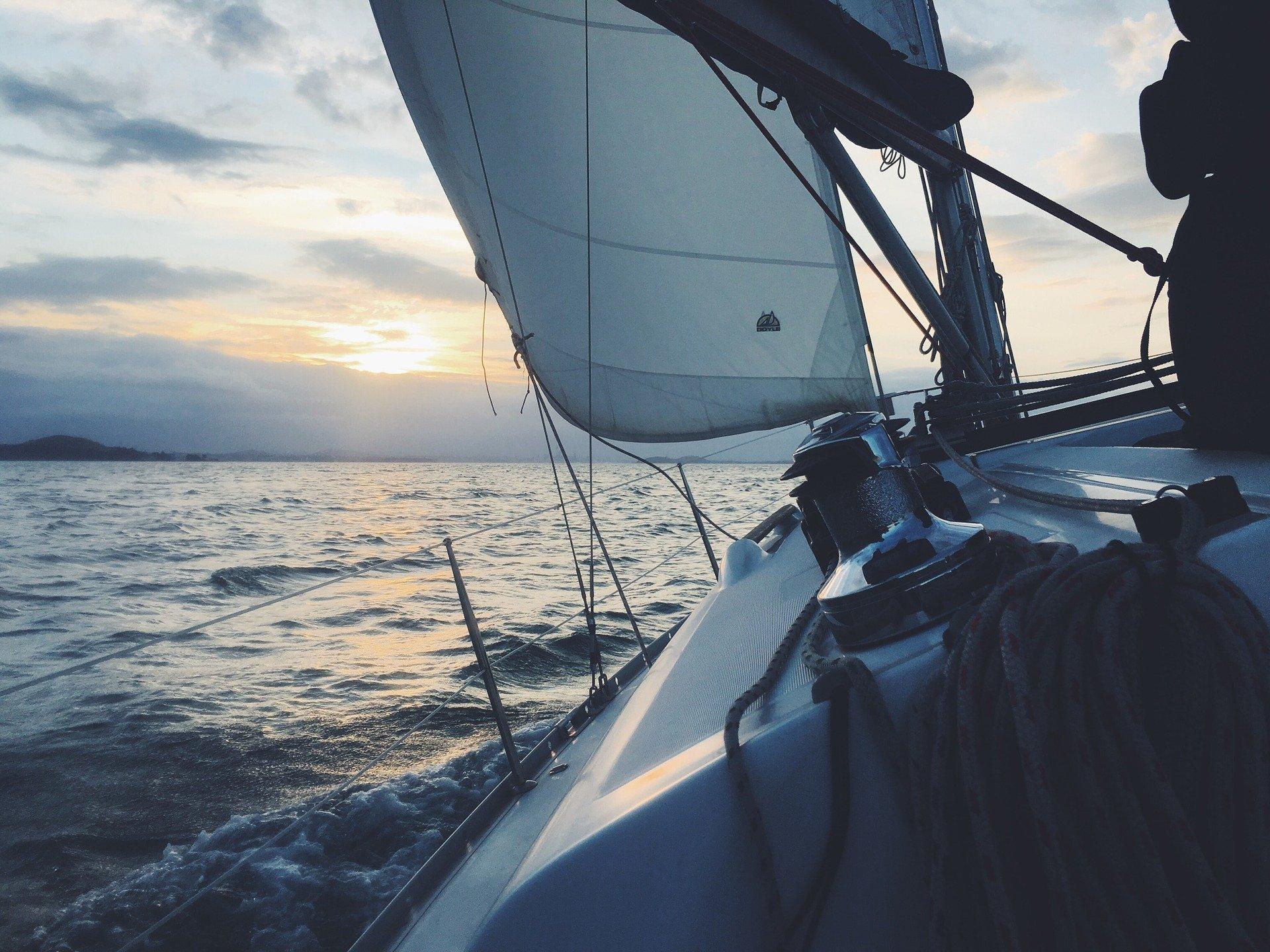 Foto de parte de um barco, vemos a vela, o mar ao lado e o céu. Imagem ilustrativa para texto seguro de barco.