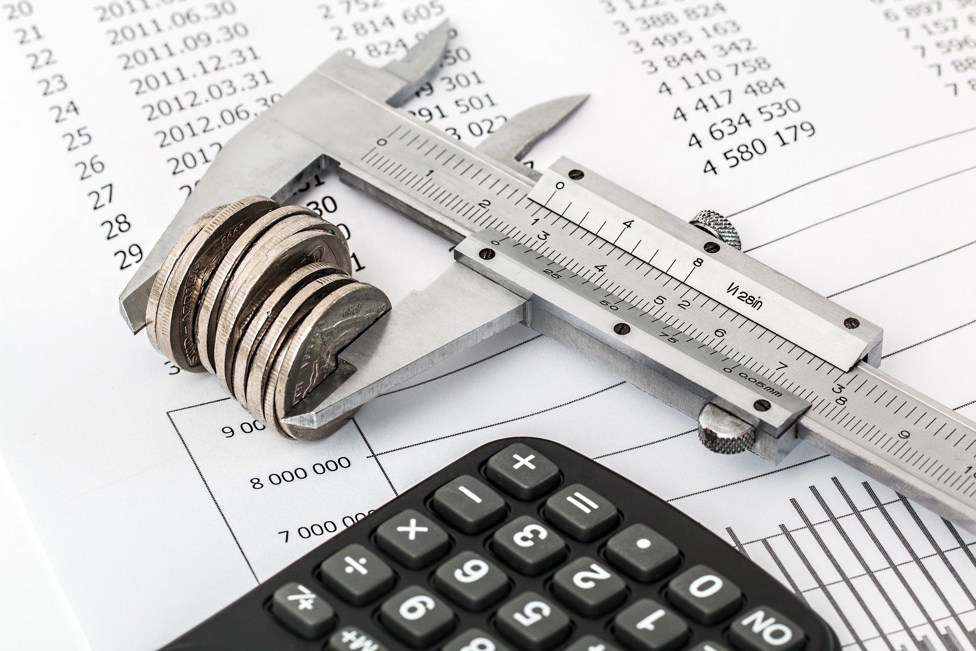 Foto de um papel com contas, em cima temos um equipamento medindo as moedas e uma calculadora preta. Imagem ilustrativa para texto seguro prestamista.