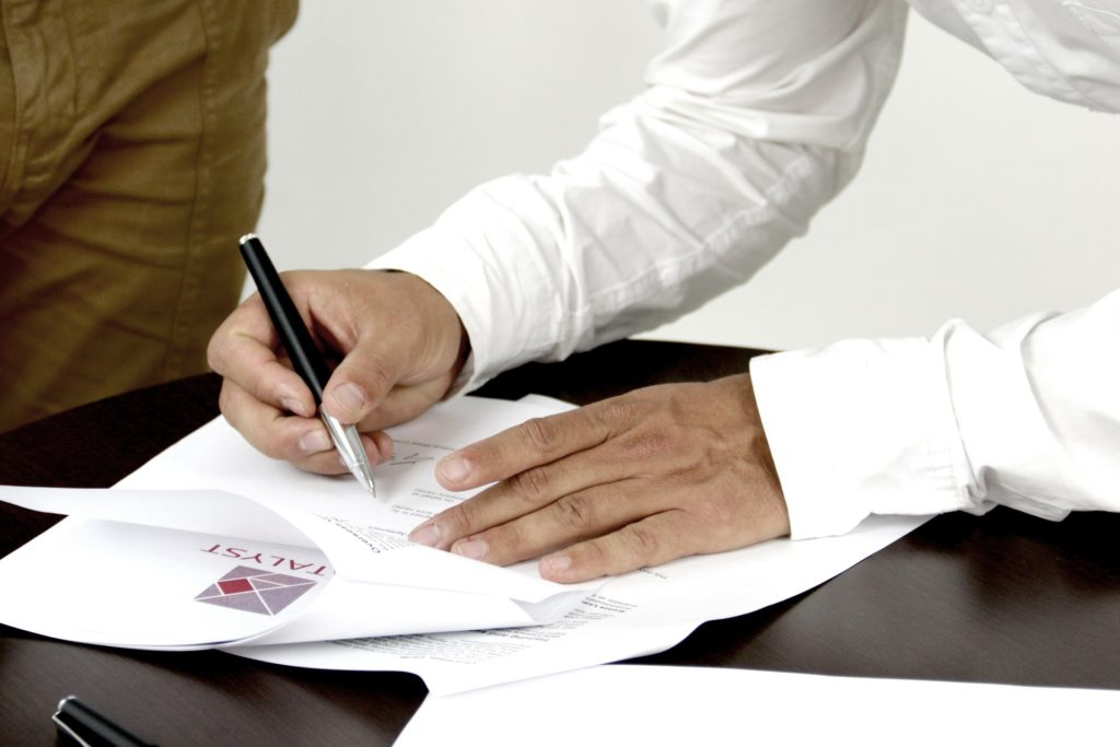 Foto de uma home de blusa branca escrevendo em papéis em cima de uma mesa preta. Imagem ilustrativa para texto seguro prestamista.