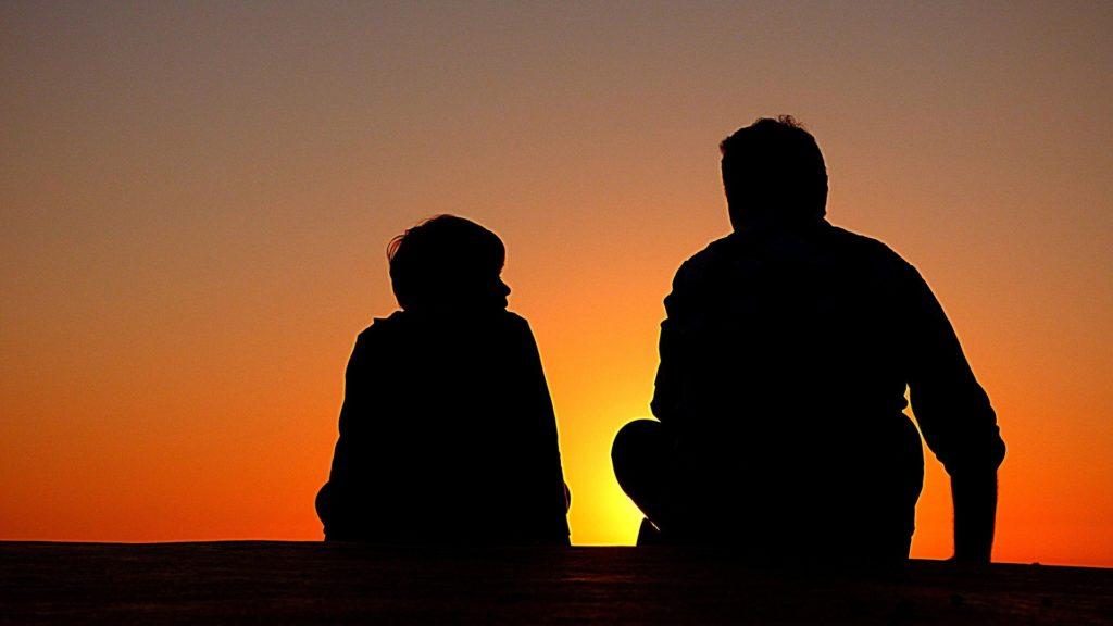 Imagem de um pai sentado ao lado do filho, não é possível ver detalhes, mas ao fundo temos um pôr do sol amarelo e laranja. Imagem ilustrativa para texto franquia de seguro de vida.