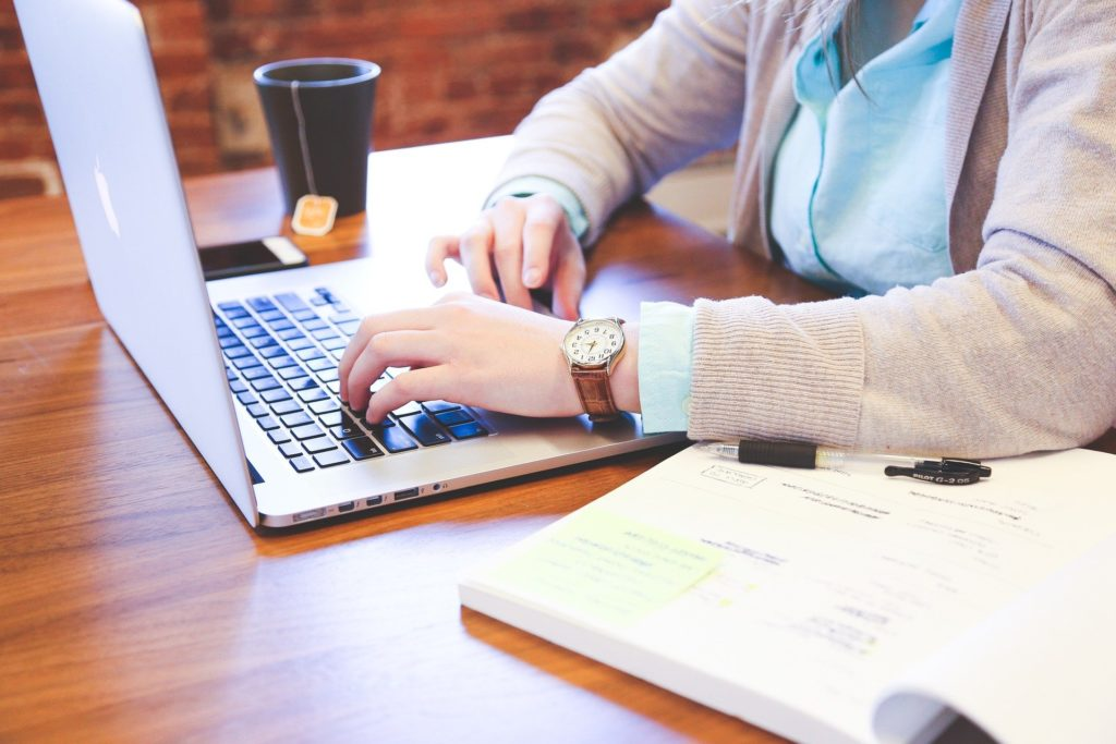 Pessoa de blusa de frio bege, em uma mesa de madeira, enquanto mexe em um computador. Ao lado vemos um livro aberto e do outro uma xícara de café preta. Imagem ilustrativa para texto endosso de seguro.