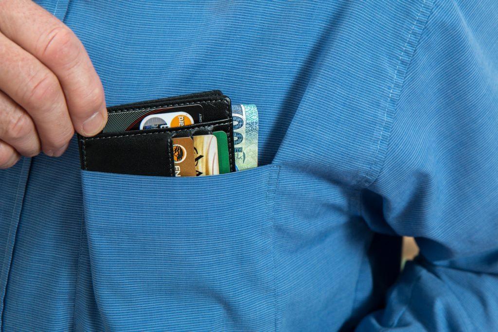 Foto do bolso de uma camisa azul, enquanto uma mão retira uma carteira preta com cartões de crédito e notas de dinheiro.