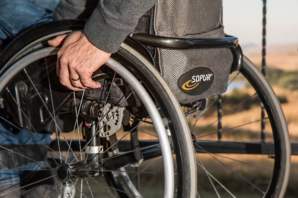 Foto de uma cadeira de rodas com uma pessoa. Toda a cadeira é preta e ao fundo vemos uma paisagem com plantas.