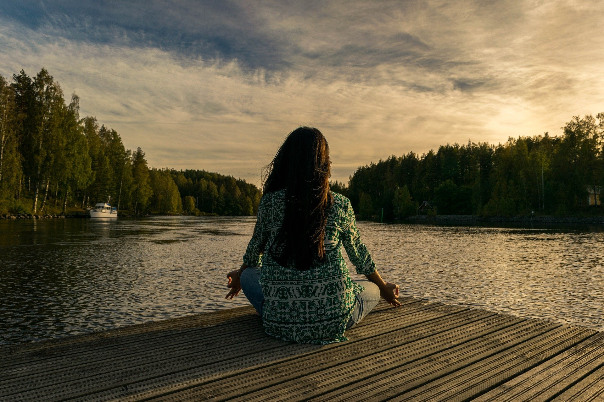 Foto de uma mulher de blusa verde sentada em uma estrutura de madeira na beira de um lado com árvores ao fundo. Imagem ilustrativa para texto seguro de vida individual.