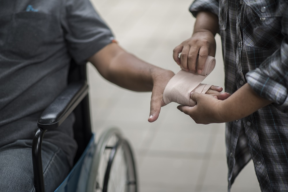Homem de roupa cinza em uma cadeira de roda, enquanto outra pessoa de blusa xadrez enfaixa a sua mão. Imagem ilustrativa para texto como funciona seguro DIT.