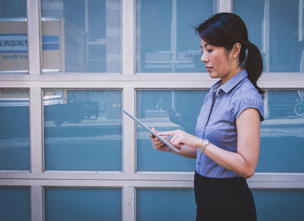 Moça de blusa azul e calça preta segurando um tablet. Ao fundo temos vidros azuis. Imagem ilustrativa para texto como funciona seguro DIT.