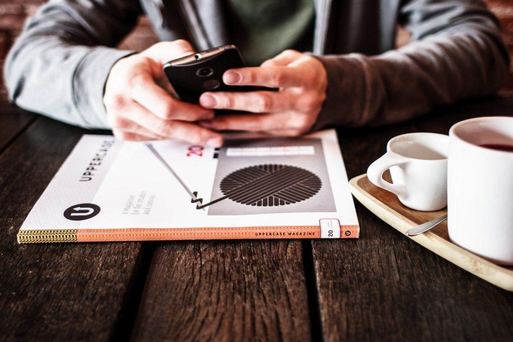 Pessoa de roupa cinza mexendo no celular. Na mesa de madeira na frente vemos um livro, uma xícara branca com café.
