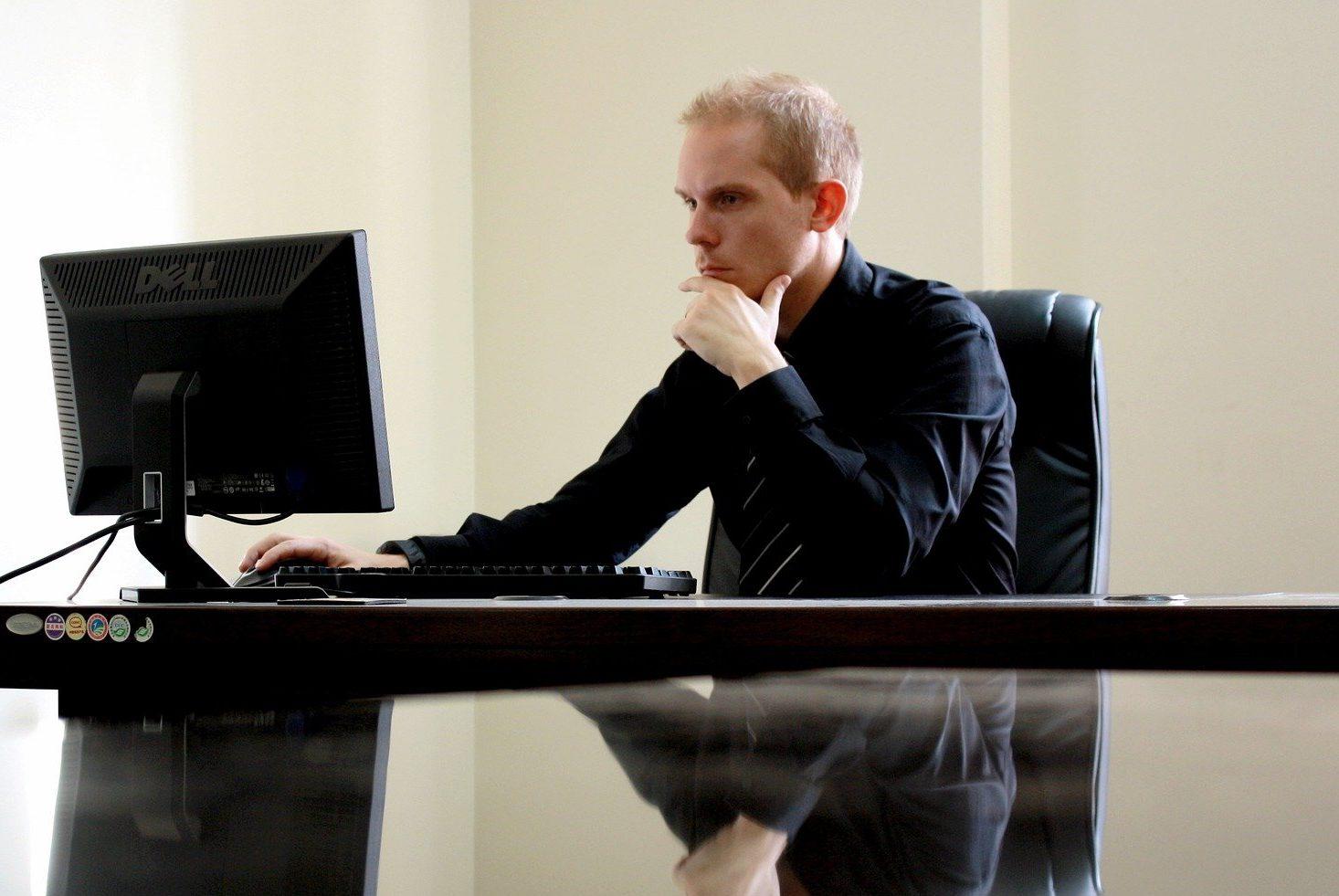 Foto de um homem de roupa preta, sentado em uma mesa tbm preta com um computador. Temos uma parede bege atrás. Imagem ilustrativa para texto corretor de seguros.