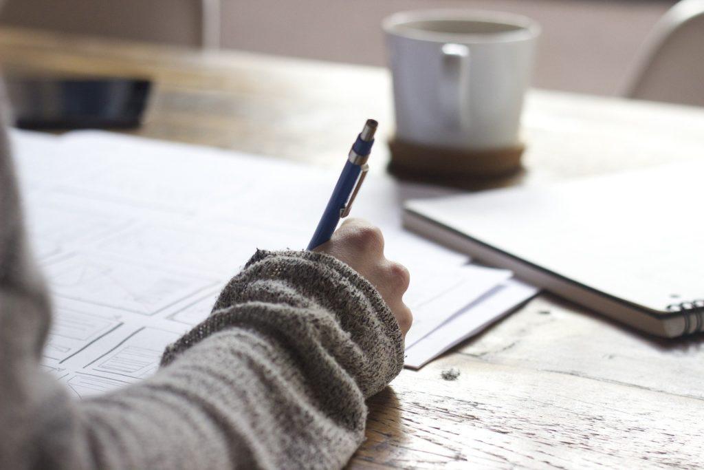Pessoa de roupa bege, segurando uma caneta azul enquanto escreve em um papel. Ao fundo vemos um caderno e uma caneca. Ilustração do texto corretor de seguros.