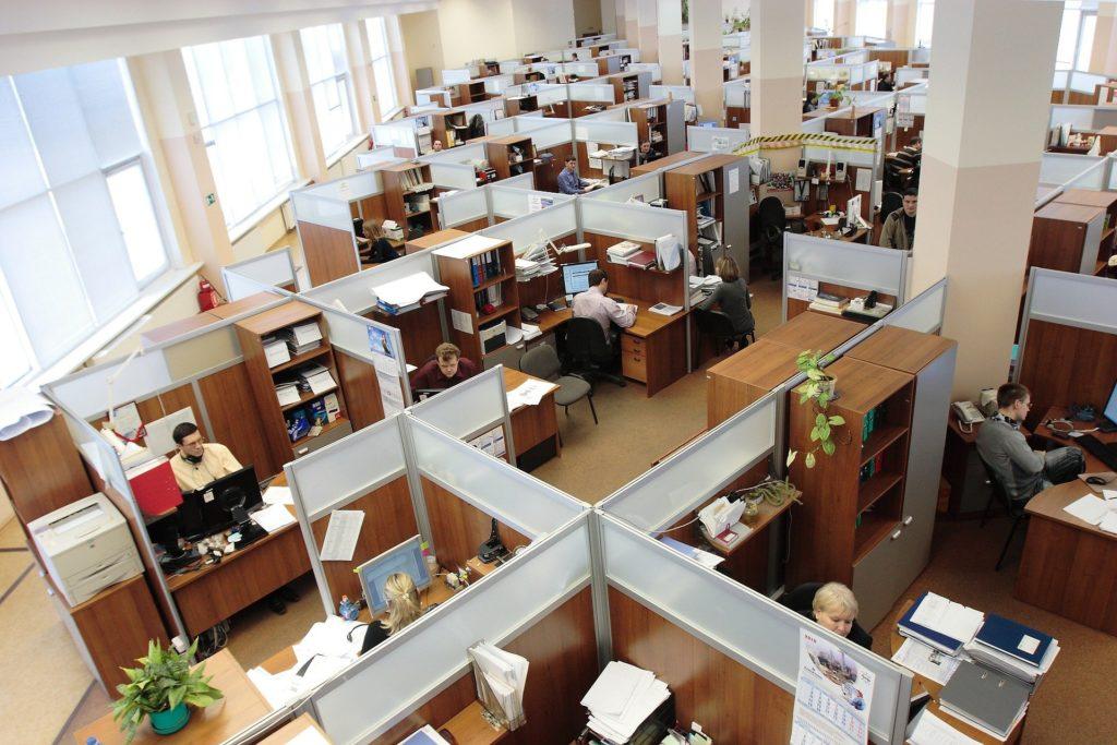 Foto de um escritório com várias cabines de madeira, pilastras brancas e mesas com trabalhadores. Ao lado vemos várias janelas. Imagem ilustrativa para texto seguro de vida para funcionários.