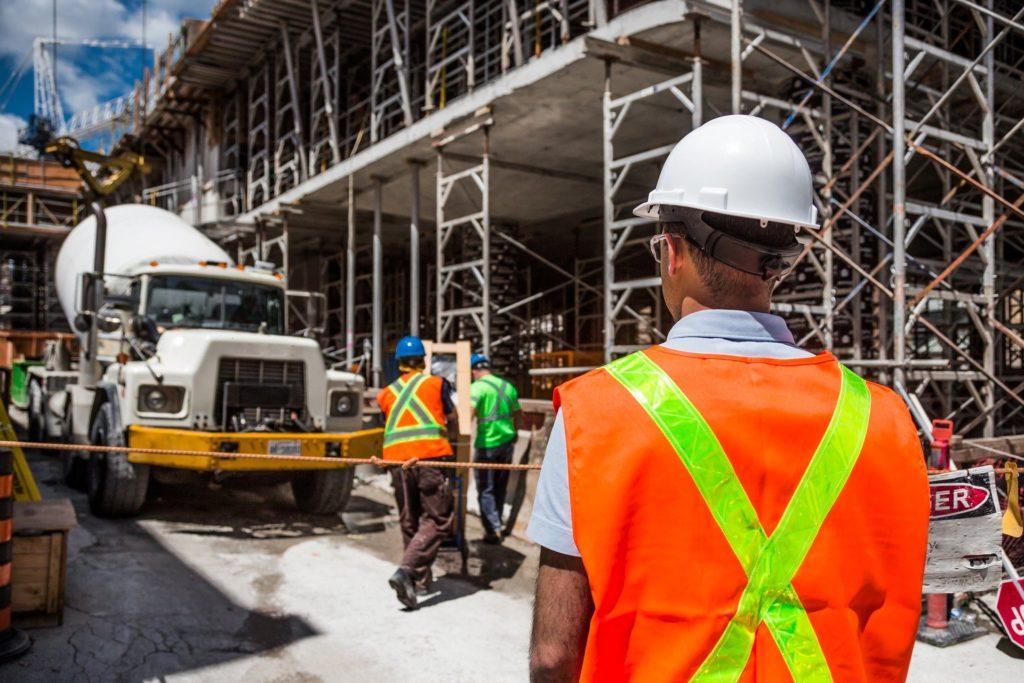 Foto de uma obra, com trabalhadores de colete laranja e capacete. Ao fundo vemos um caminho branco e partes da obra com pilastras. Imagem ilustrativa para texto seguro de vida para funcionários.