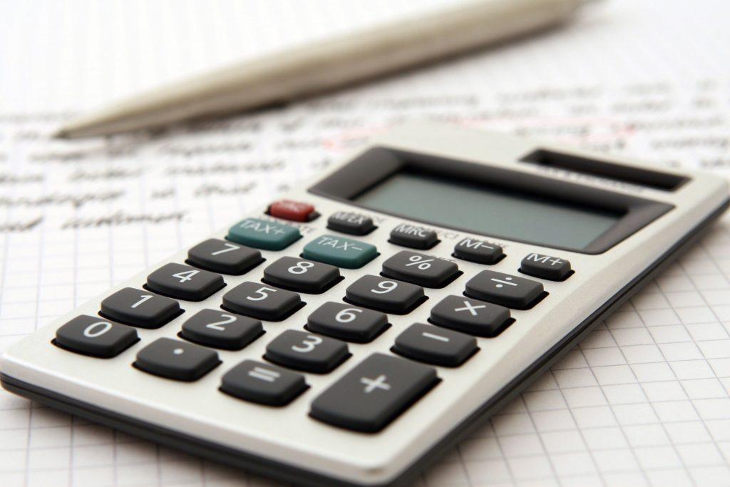 Foto de uma calculadora cinza, com um papel com escritos ao fundo e uma caneta ao lado. Imagem ilustrativa para texto seguro de vida para funcionários.