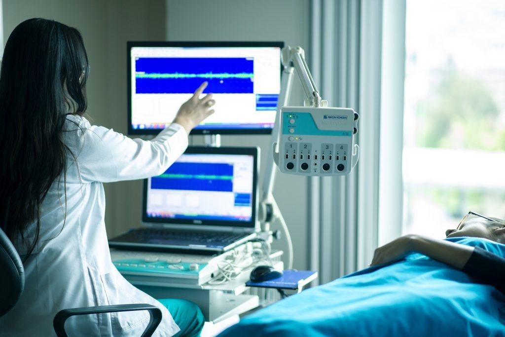 Médica de jaleco, aprontando para uma máquina, enquanto temos uma paciente deitada em uma maca ao lado. Temos objetos azuis, uma cortina e uma janela ao fundo.