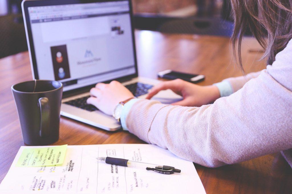 Mulher de blusa bege, utilizando um computador em uma mesa de madeira, com uma caneca preta, e um caderno branco ao lado. Ilustração do texto seguro de vida para funcionários.