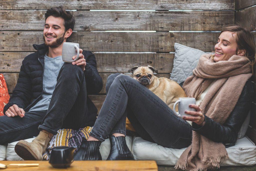 Foto de um homem com roupa preta sentado ao lado de uma mulher com cachecol bege. Vemos uma mesa de madeira no meio, um sofá cinza e uma parede de madeira. Temos um cachorro no colo da mulher.