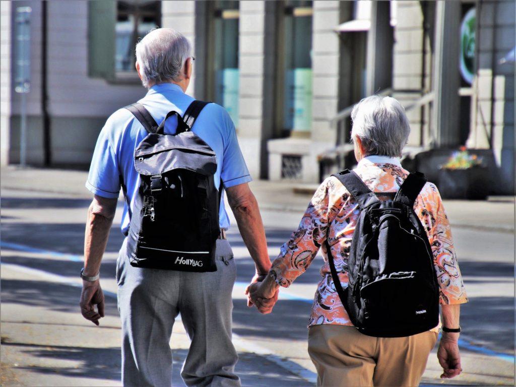 Um senhor de blusa azul com mochila preta, dando a mão para uma senhora de blusa estampada laranja também de mochila. Ambos caminham em uma rua. Imagem ilustrativa para texto seguro de vida sênior.