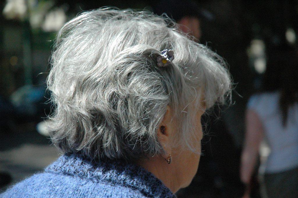 Foto de uma senhora por trás, usando blusa azul. Ao fundo vemos outras pessoas a uma rua. Ilustração do texto seguro de vida sênior.